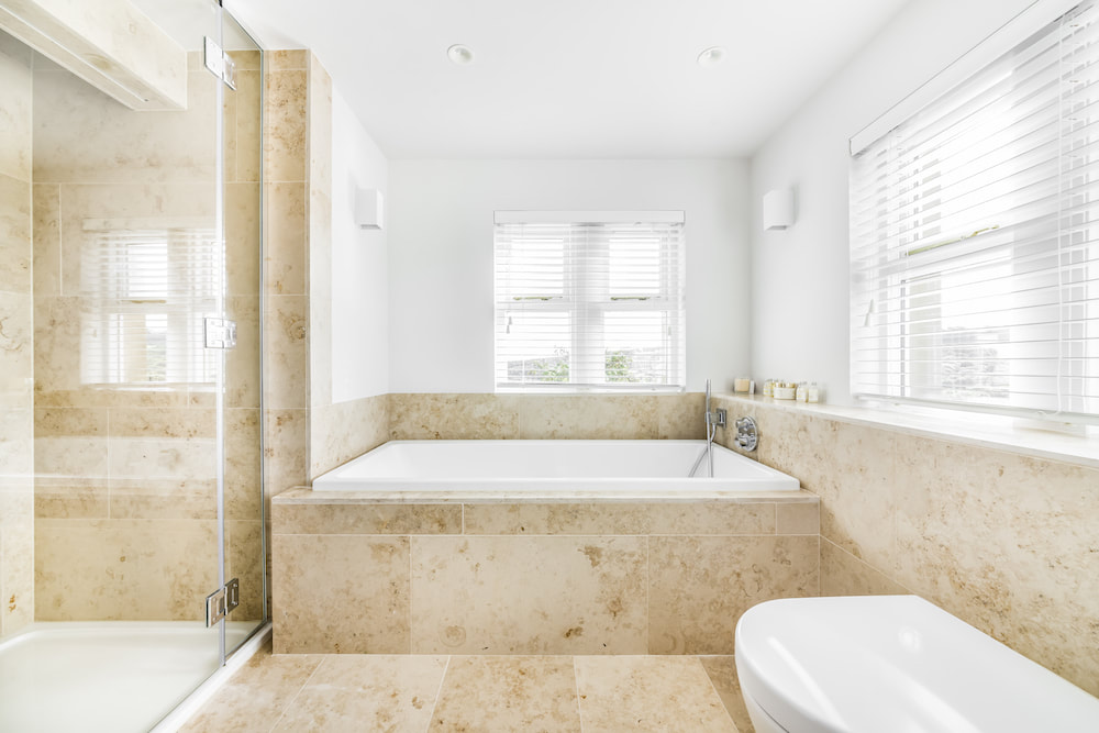 The shower and bath in the house bathroom which benefits from natural light.